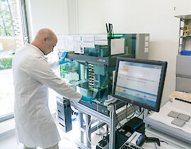 Staff member of the Central Biobank Charité, Berlin (ZeBanC) uses a robot to isolate DNA from blood samples of the National Register.