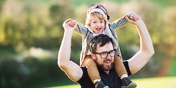 Young father carries son on his shoulders, fotolia.com | Halfpoint